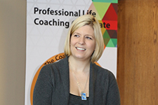Anne standing in front of the Professional Life Coaching banner