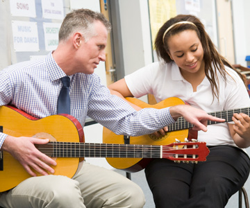 decorative image: photo of an instructor working with a student learning to play guitar