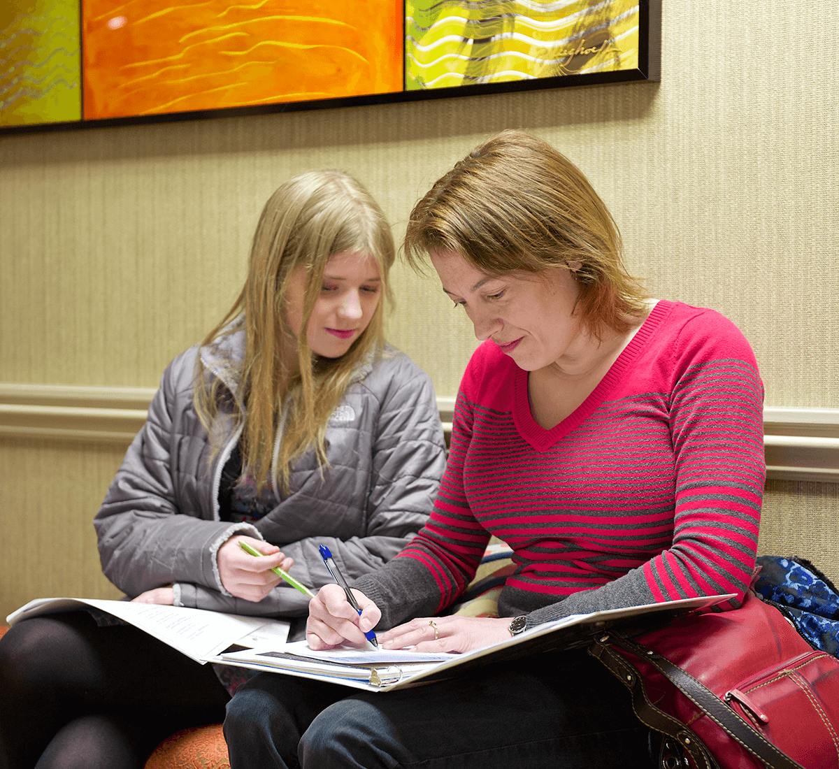 two women talking while looking at a notebook