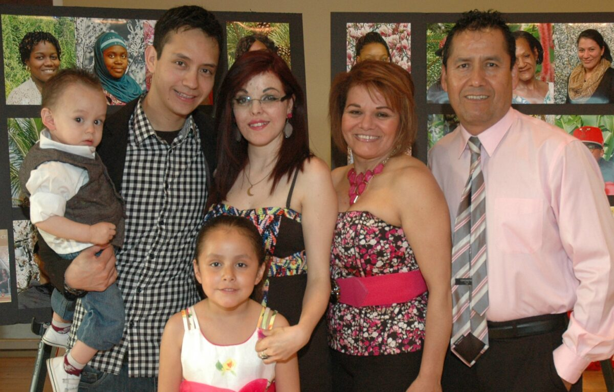 Woman standing with her partner, parents, and two children