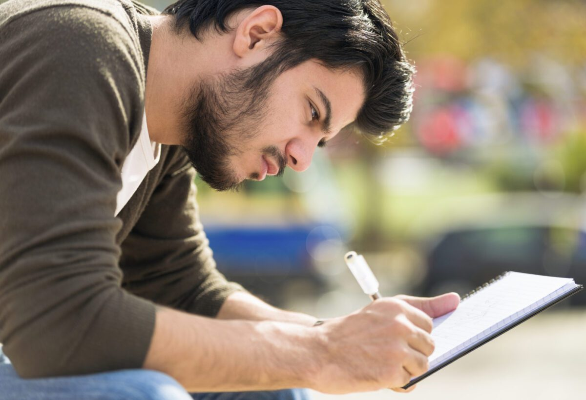 man writing in his journal