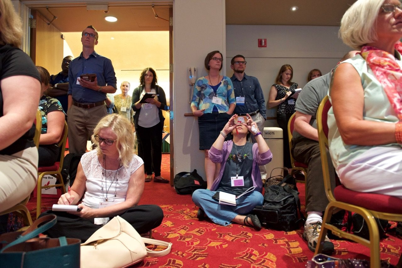 woman sitting on the floor taking pictures in packed breakout session