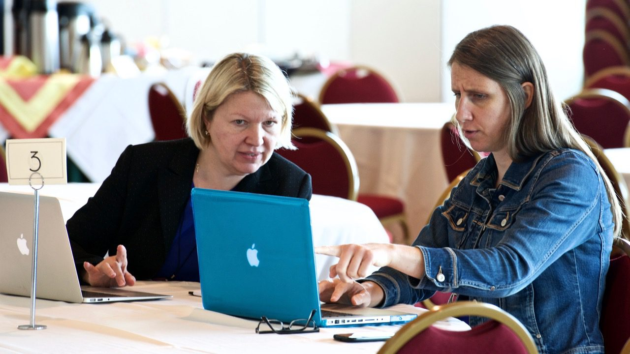 women talking while pointing at computer