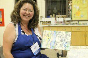 Arlene Schneller showing off art