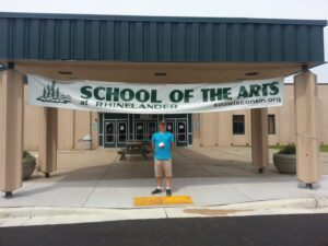 man poses in front of The School of the Arts in Rhinelander