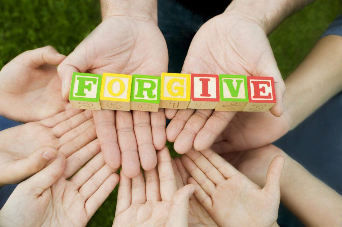 hands holding blocks spelling forgive