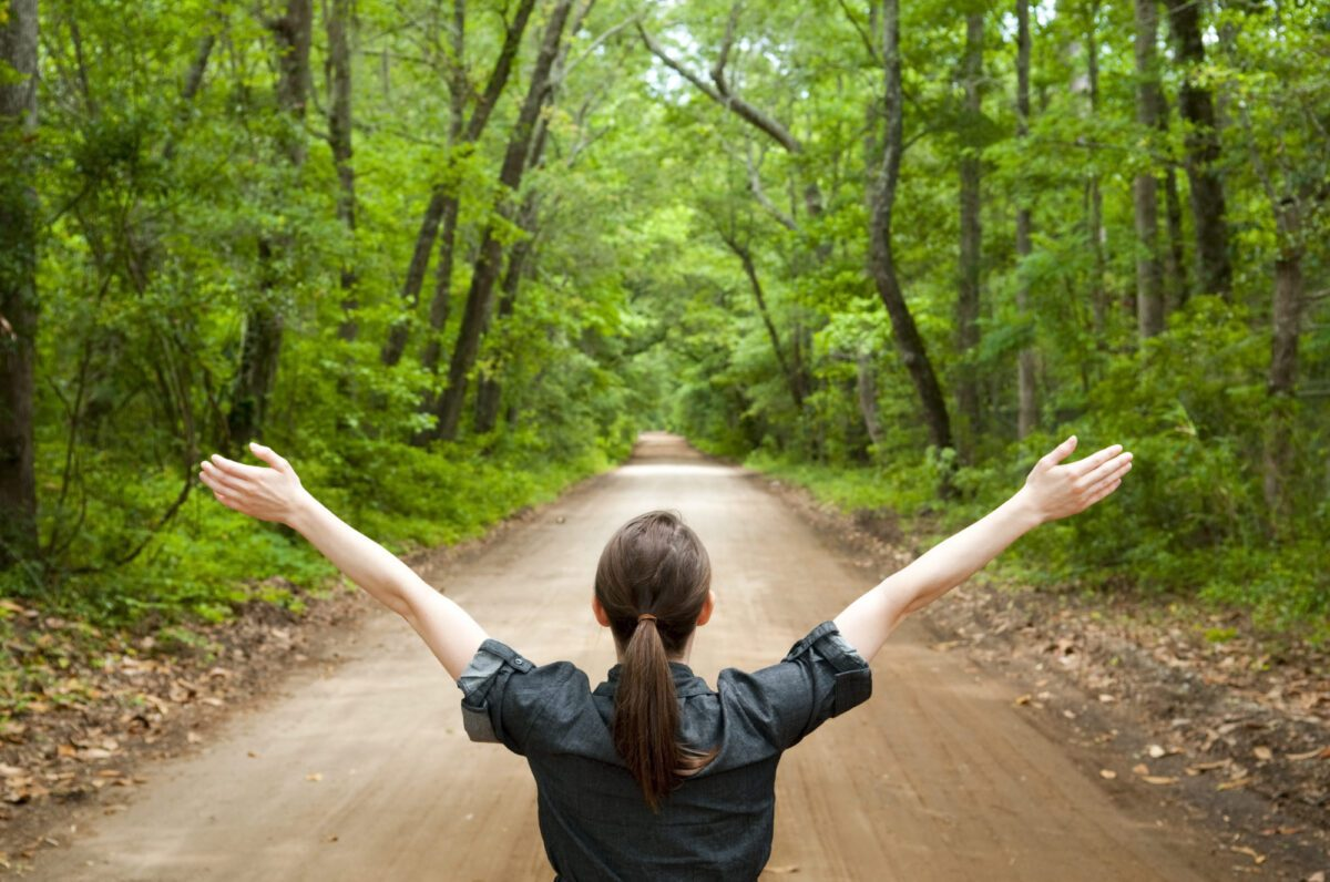 woman with arms outstretched on wooded path