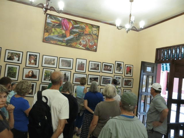 group looks at drawings on how cacao is processed at La Casa del Chocolate in Baracoa