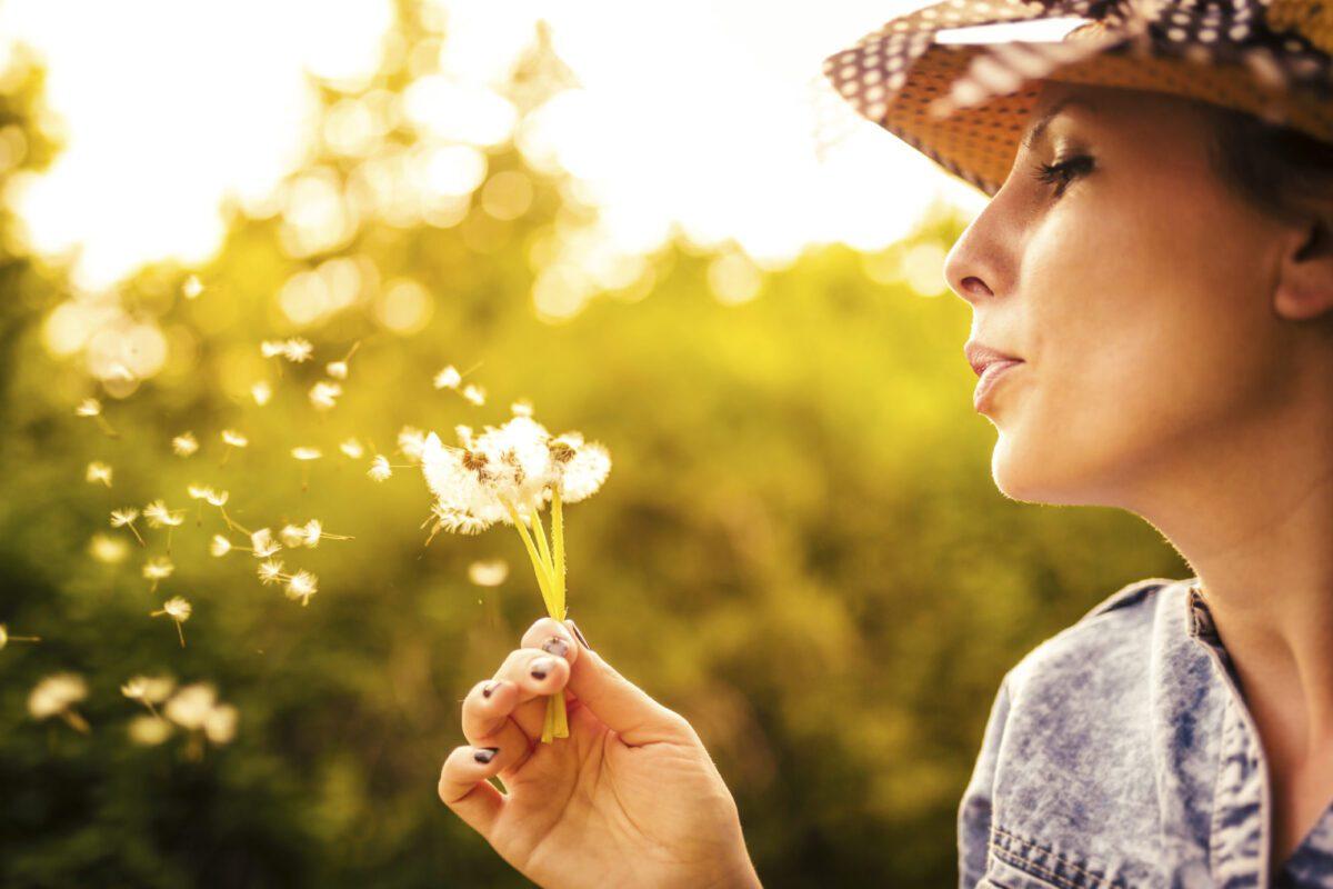 woman blowing on dandelion