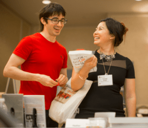 two people talking at a book sale