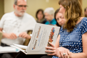group blurred with Writers' Institute binder in the foreground