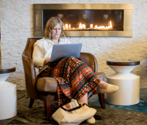 woman typing by the fireplace