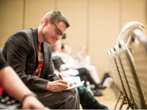 man writes in notebook in row of attendees
