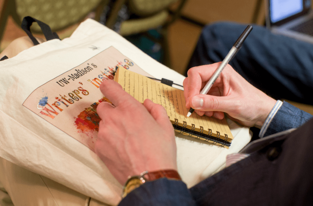 person writing in notebook with Writer's Instute bag as background