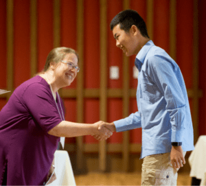 ACE student receive certificate and a handshake