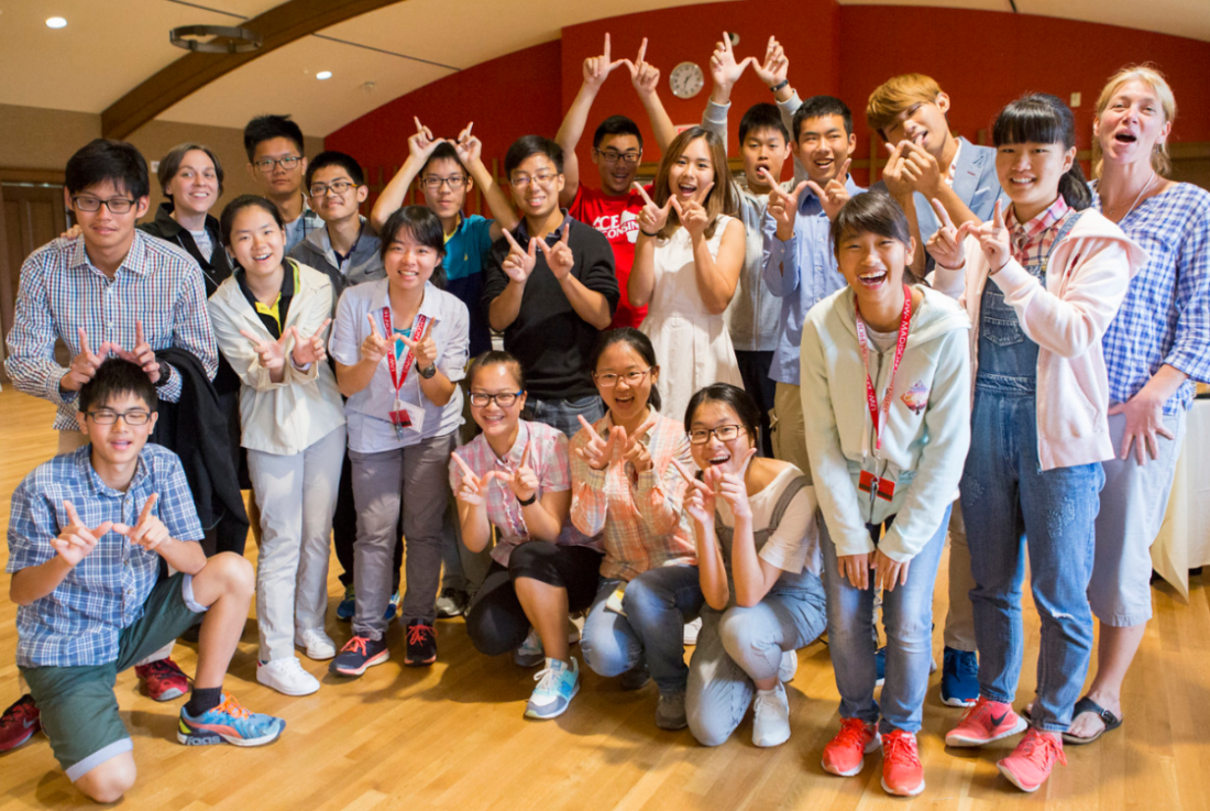 International students smile together and put up a W using their hands