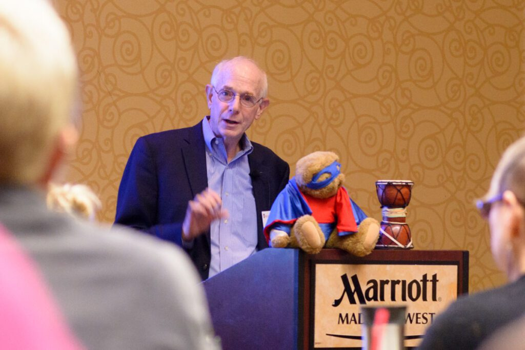 Richard Kagan talking from podium with a stuff bear and a drum