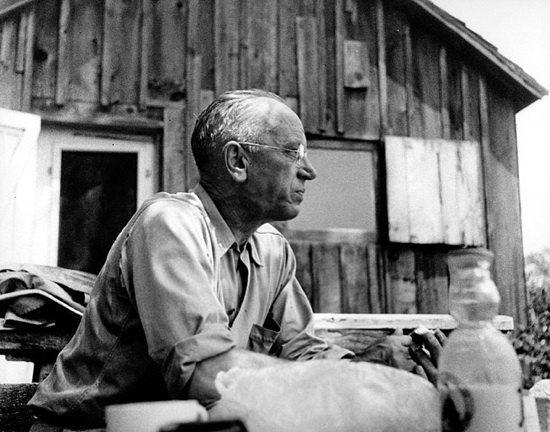 Aldo Leopold in front of barn looking pensive