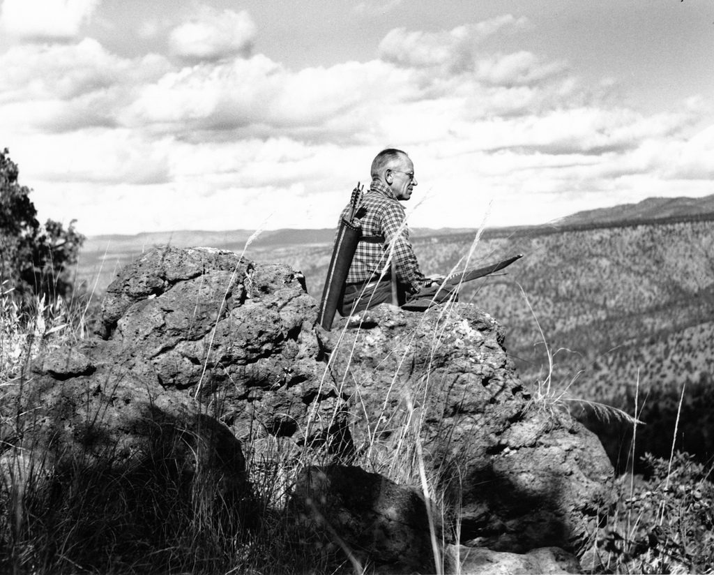 Aldo Leopold sitting on the edge of a rock, looking out over the land