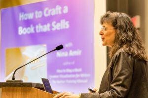 Nina Amir talking in front of presentation slide