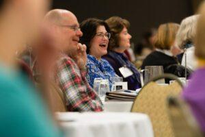 woman at at table laughing at presentation