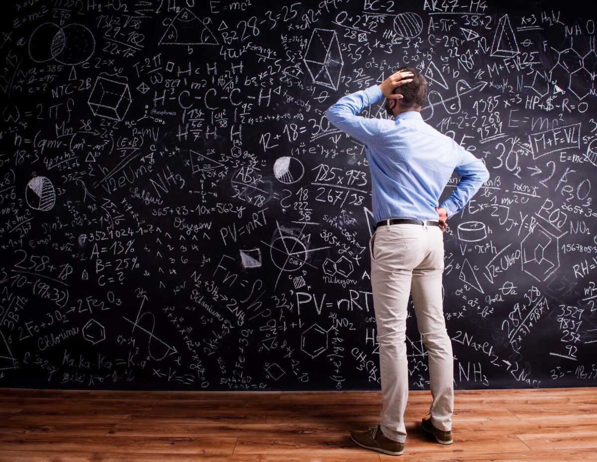 teacher in front of blackboard with math symbols