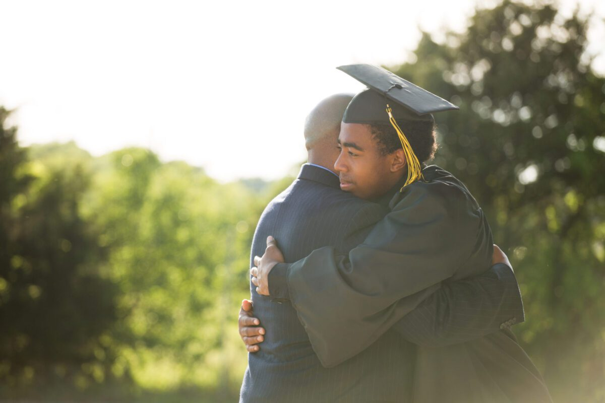 father hugging son on graduation day