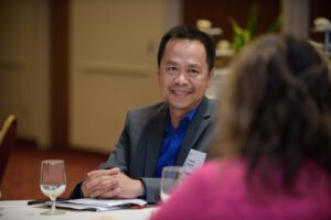 man smiling while talking to conference participant