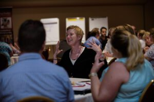 woman gestures with hands while talking at conference