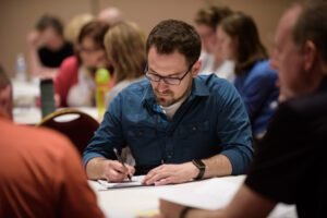 conference attendee writing at his table