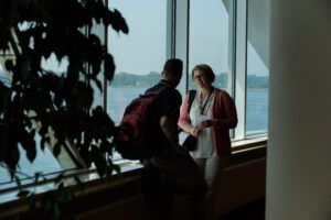 two people talk in front of the windows at Monona Terrace