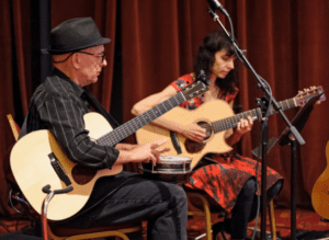 two people playing guitar and a drum