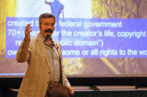 presenter in front of a giant presentation slide