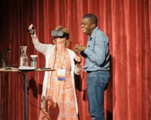 woman with VR glasses standing by man laughing