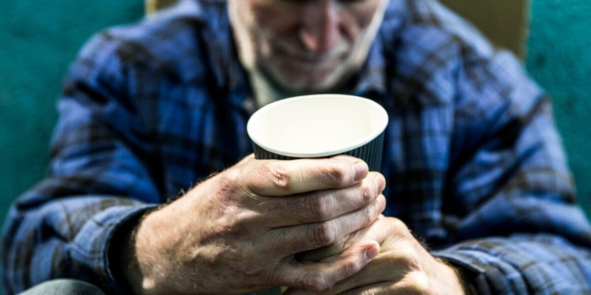 older man with heavy clothes grasping a paper cup
