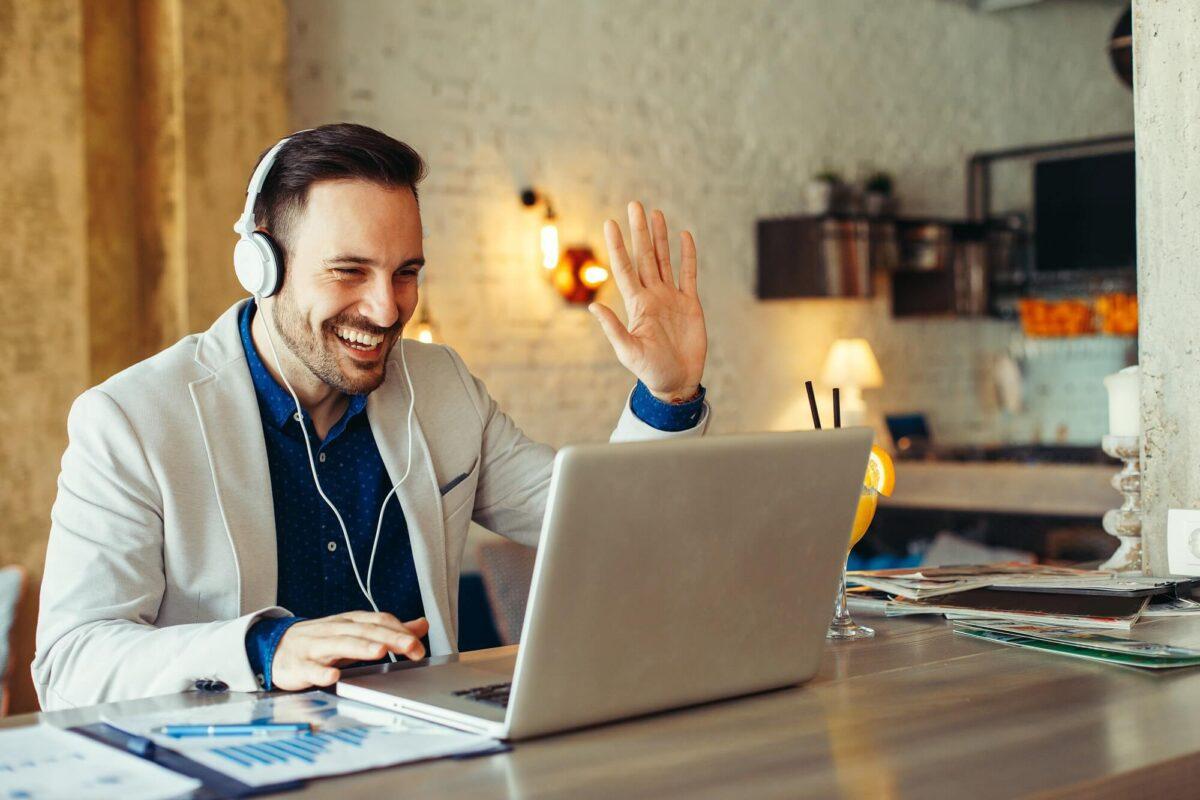 Man waving to computer screen