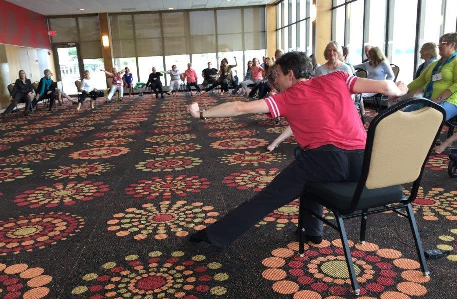 People with Parkinson's disease participate in a dance-like exercise from their chairs