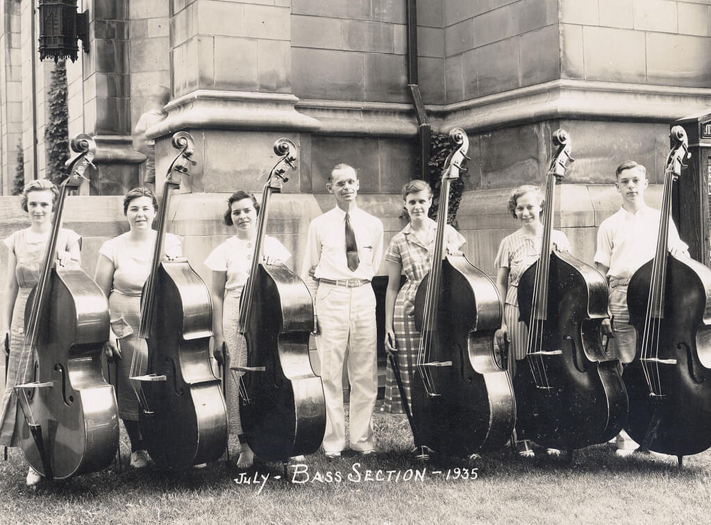 six bass students standing with their instruments and teacher in front of university building