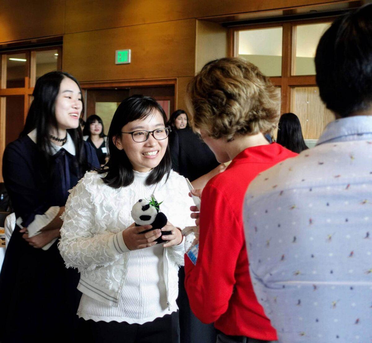 student holds panda bear toy