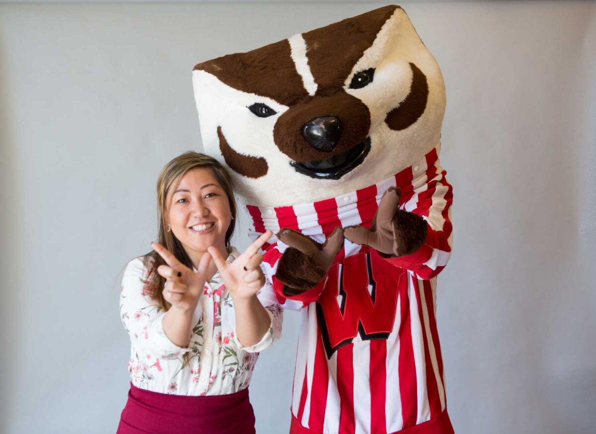 """Bucky Badger with a returning adult student giving the """"W"""" sign"""