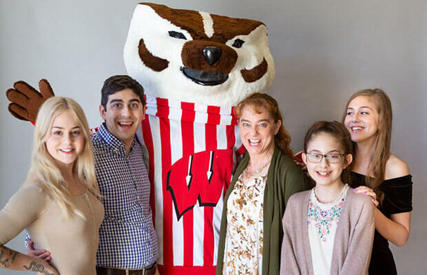 Some returning adult students like Nicole Metko (to Bucky's right) are motivated by seeing their children excel in school.
