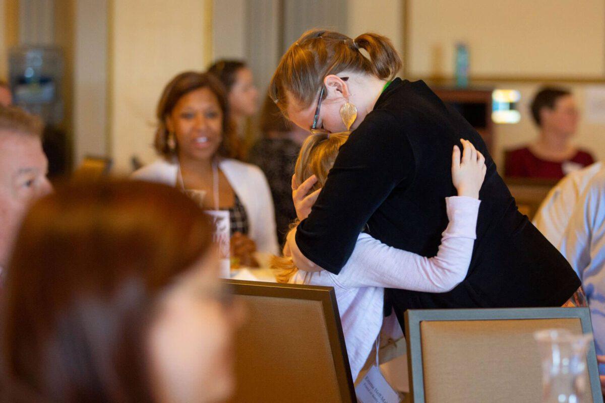 ACCSS student receiving 2019 scholarship hugs daughter