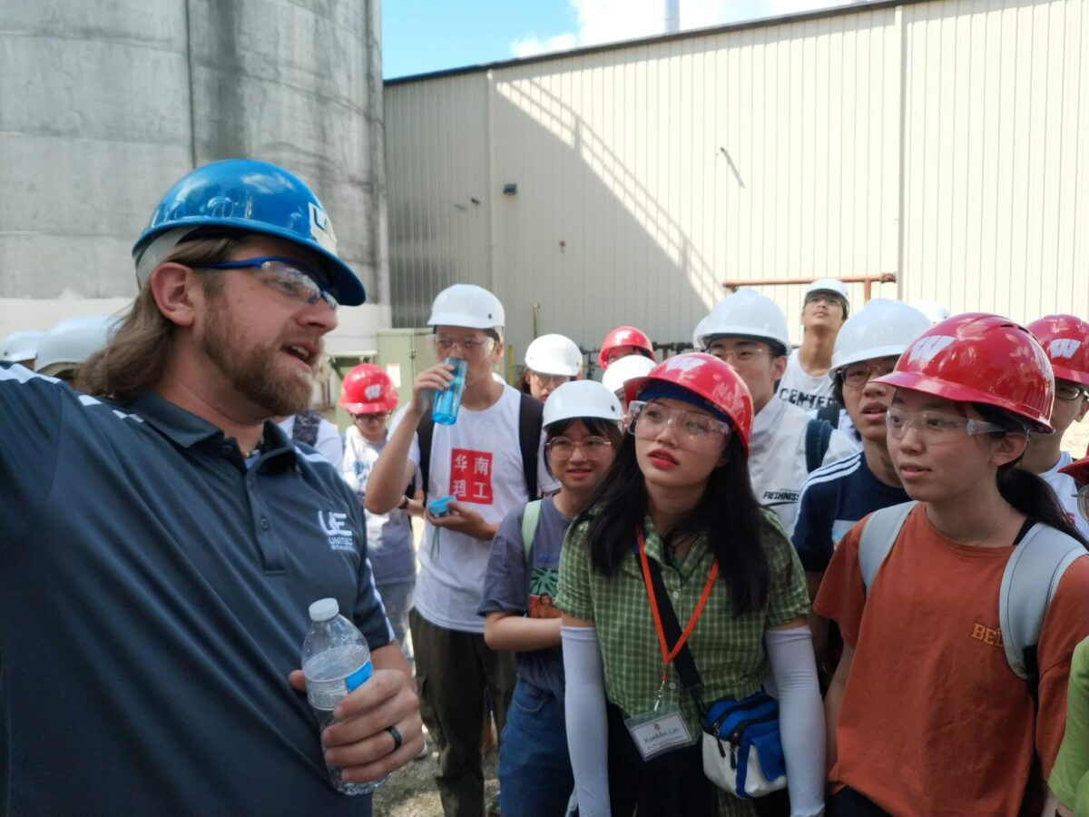 Chinese students touring United Ethanol in Milton; wearing hardhats listening to a speaker standing outside near industrial buildings