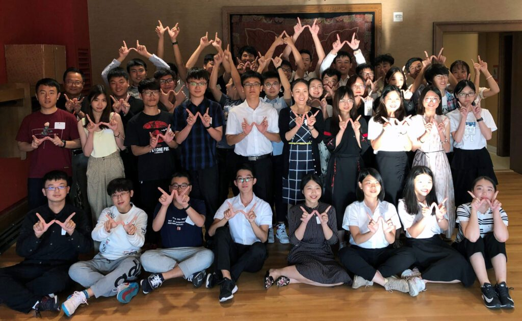 """group of Chinese students posing for a picture, making the UW-Madison """"W"""" signs"""