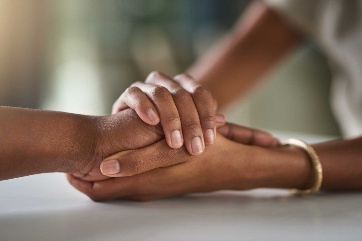 sets of hands holding on a table