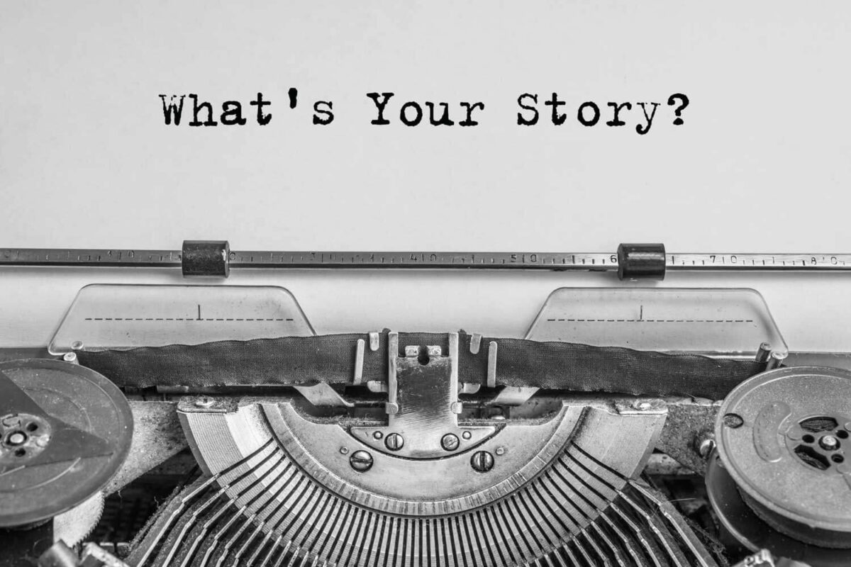 """black and white photo of a typewriter with """"what's your story"""" typed out on a white piece of paper"""