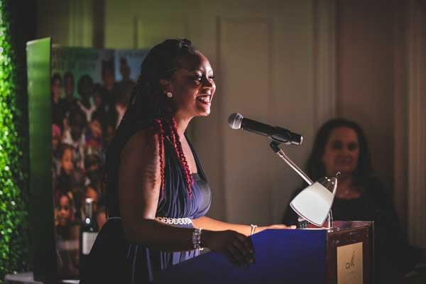 Keena Atkinson speaking at a podium at the Odyssey/Madion Club gala
