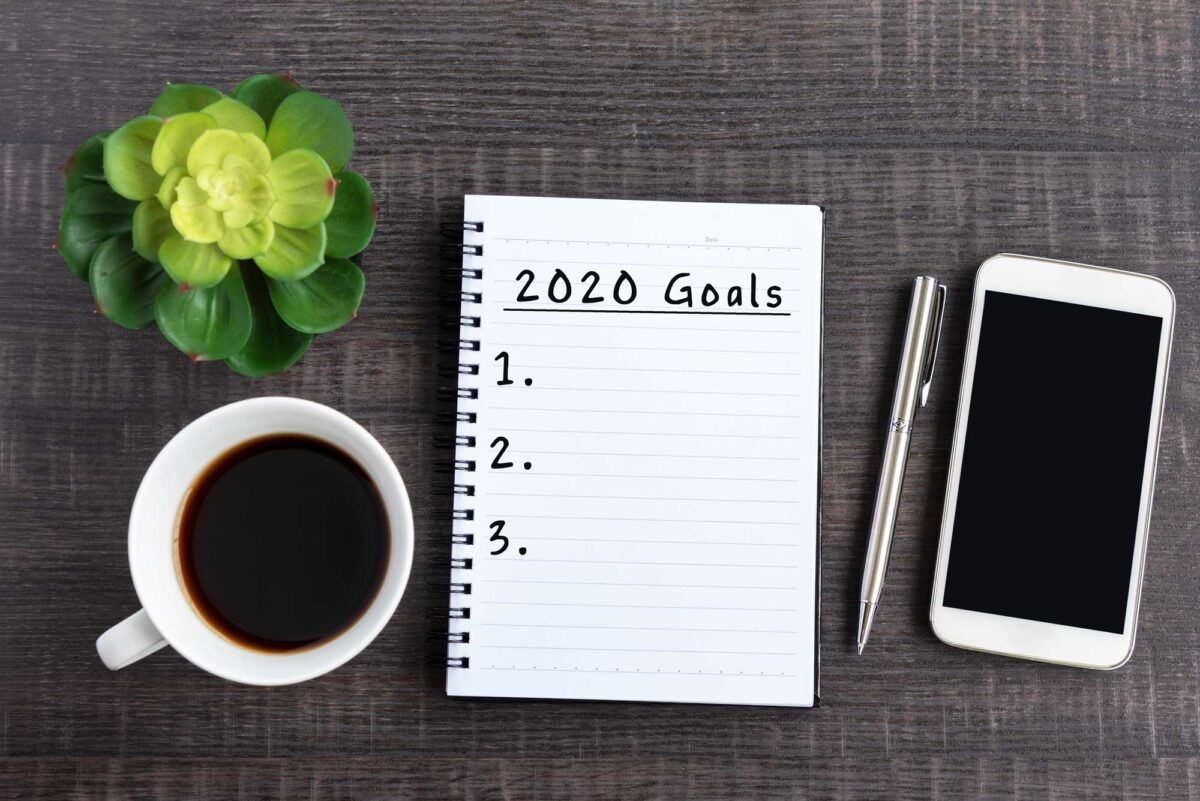 """notebook with """"2020 goals"""" sitting next to coffee cup and phone and pen"""