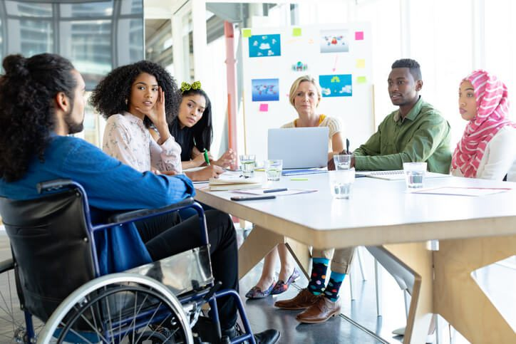 group of people sitting around a table, including a person in a wheelchair and people of color