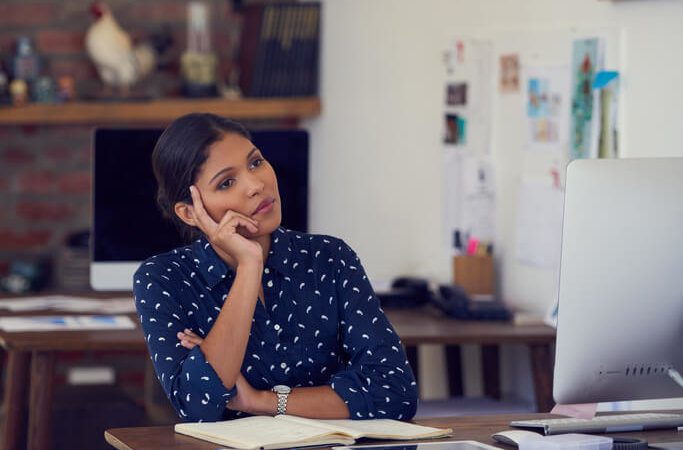 Shot of a young businesswoman looking thoughtful while working at her desk in a modern office